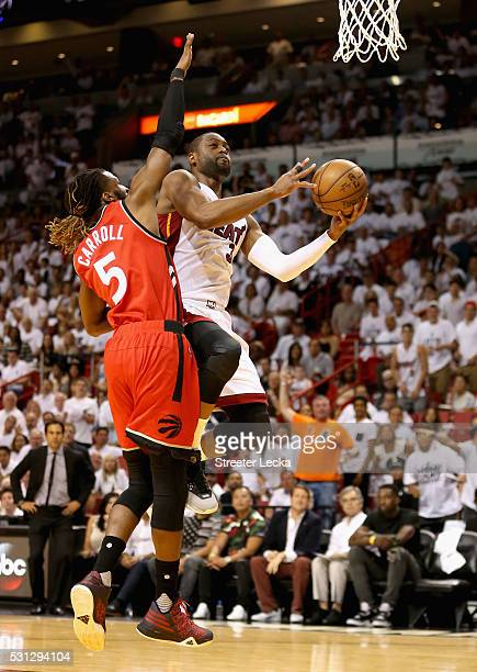 Dwyane Wade of the Miami Heat drives to the basket against DeMarre Carroll of the Toronto Raptors during Game 6 of the Eastern Conference Semifinals...