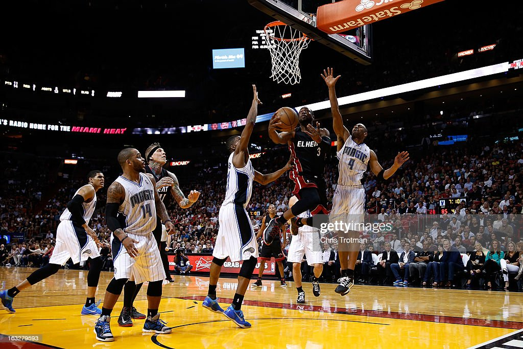 Dwyane Wade #3 of the Miami Heat drives to the basket past Moe Harkless #21 and Arron Afflalo #4 of the Orlando Magic at American Airlines Arena on March 6, 2013 in Miami, Florida.