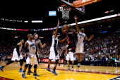 Dwyane Wade of the Miami Heat drives to the basket past Moe Harkless and Arron Afflalo of the Orlando Magic at American Airlines Arena on March 6...