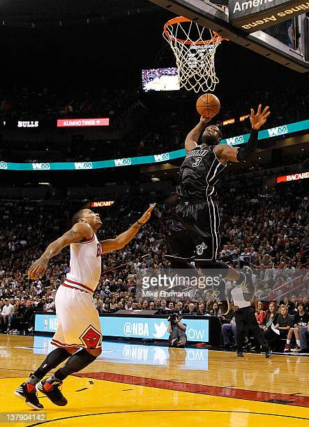 Dwyane Wade of the Miami Heat dunks over Derrick Rose of the Chicago Bulls during a game at American Airlines Arena on January 29 2012 in Miami...