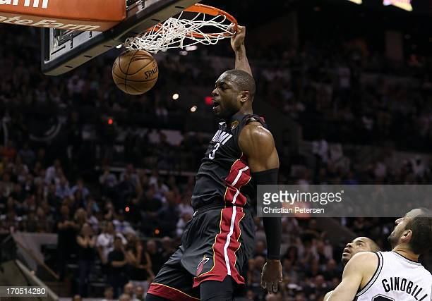 Dwyane Wade of the Miami Heat dunks the ball in front of Manu Ginobili of the San Antonio Spurs in the fourth quarter during Game Four of the 2013...