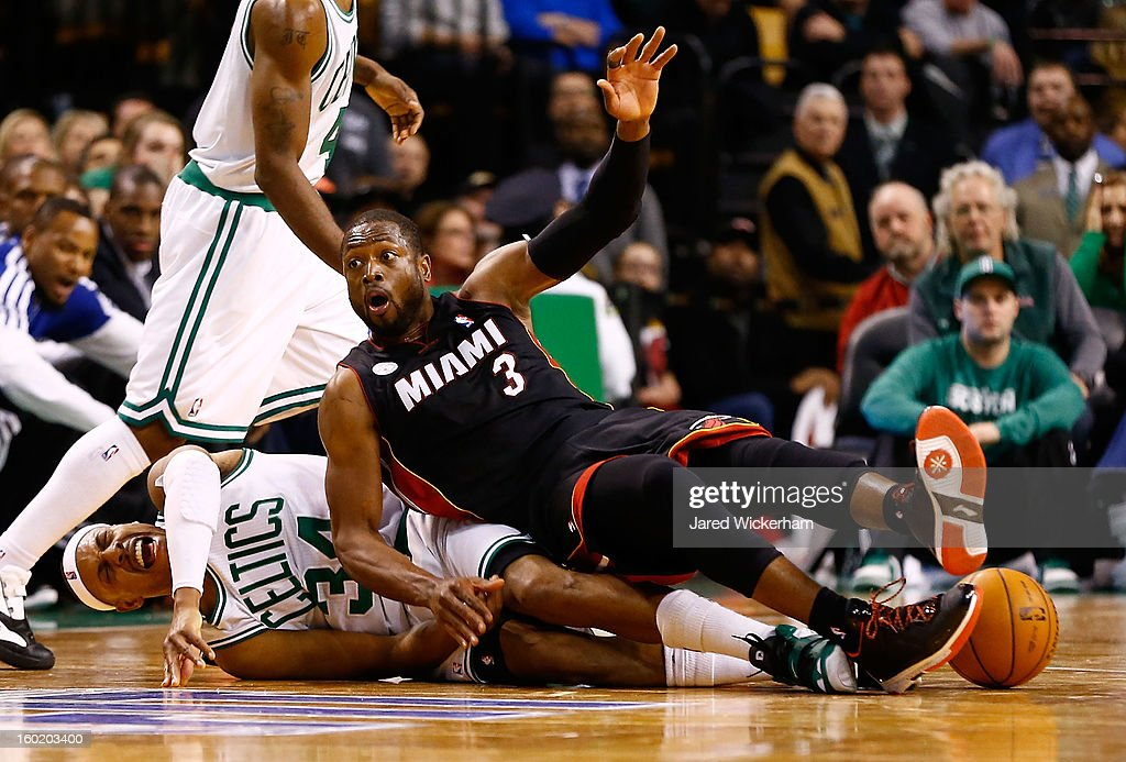 Dwyane Wade #3 of the Miami Heat falls on top of Paul Pierce #34 of the Boston Celtics after scrambling for a loose ball during the game on January 27, 2013 at TD Garden in Boston, Massachusetts.