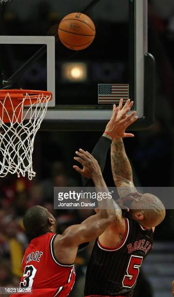 Dwyane Wade of the Miami Heat gets his hand into the face of Carlos Boozer of the Chicago Bulls as they try to rebound at the United Center on...