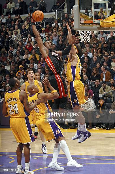 Dwyane Wade of the Miami Heat goes strong to the basket against Vladimir Radmanovic Maurice Evans Luke Walton and Kobe Bryant of the Los Angeles...