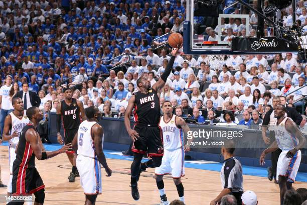 Dwyane Wade of the Miami Heat goes to the basket between Kendrick Perkins Thabo Sefolosha and Serge Ibaka of the Oklahoma City Thunder during Game...