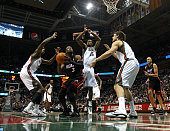 Dwyane Wade of the Miami Heat goes up for a shot against Larry Sanders John Salmons and Andrew Bogut of the Milwaukee Bucks at the Bradley Center on...