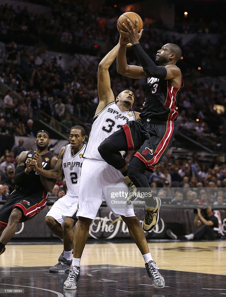 Dwyane Wade #3 of the Miami Heat goes up for a shot over Boris Diaw #33 of the San Antonio Spurs in the third quarter during Game Four of the 2013 NBA Finals at the AT&T Center on June 13, 2013 in San Antonio, Texas.