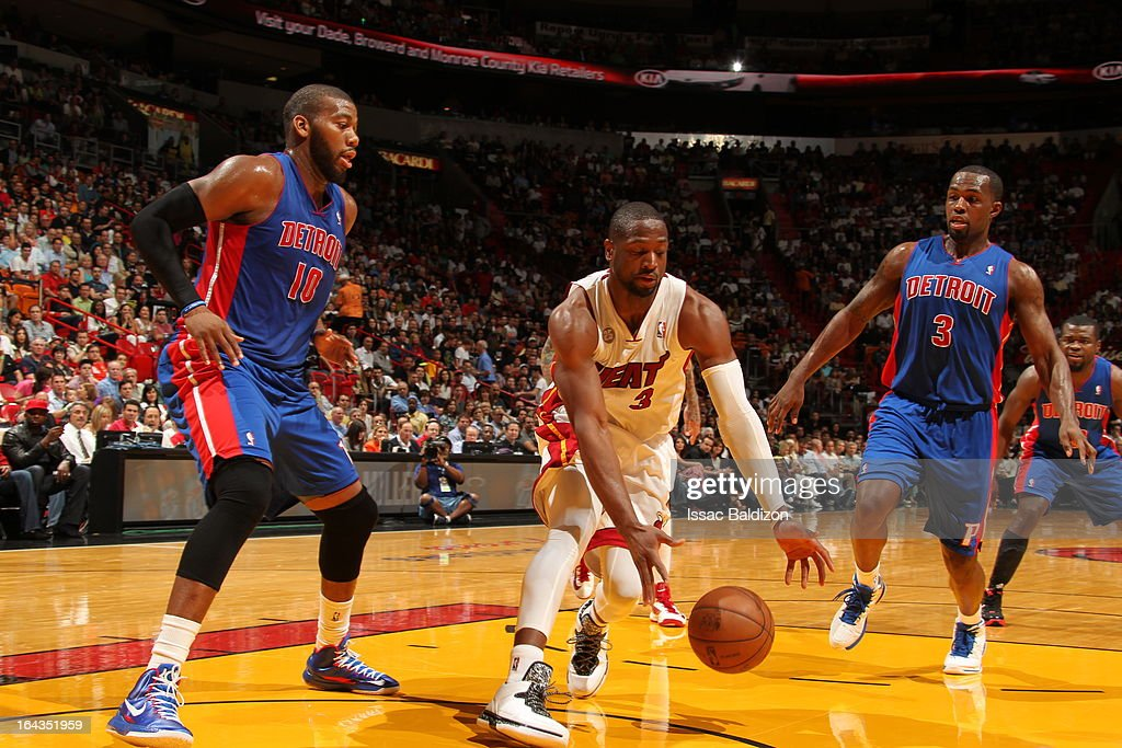 Dwyane Wade #3 of the Miami Heat grabs a loose ball against Greg Monroe #10 and Rodney Stuckey #3 of the Detroit Pistons on March 22, 2013 at American Airlines Arena in Miami, Florida.