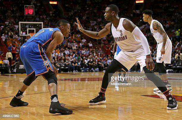 Dwyane Wade of the Miami Heat guards Russell Westbrook of the Oklahoma City Thunder during a game at American Airlines Arena on December 3 2015 in...