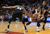 Dwyane Wade of the Miami Heat has the ball stripped by Giannis Antetokounmpo and John Henson of the Milwaukee Bucks during a game at American...