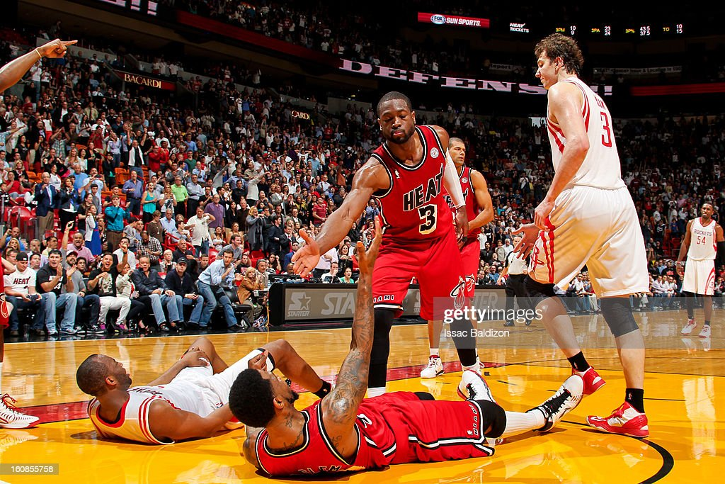 <a gi-track='captionPersonalityLinkClicked' href=/galleries/search?phrase=Dwyane+Wade&family=editorial&specificpeople=201481 ng-click='$event.stopPropagation()'>Dwyane Wade</a> #3 of the Miami Heat helps up teammate <a gi-track='captionPersonalityLinkClicked' href=/galleries/search?phrase=Udonis+Haslem&family=editorial&specificpeople=201748 ng-click='$event.stopPropagation()'>Udonis Haslem</a> #40 while playing against the Houston Rockets on February 6, 2013 at American Airlines Arena in Miami, Florida.