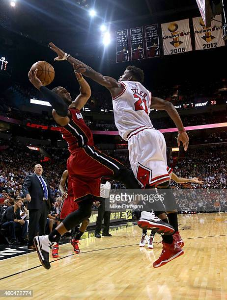 Dwyane Wade of the Miami Heat is defended by Jimmy Butler of the Chicago Bulls during a game at American Airlines Arena on December 14 2014 in Miami...