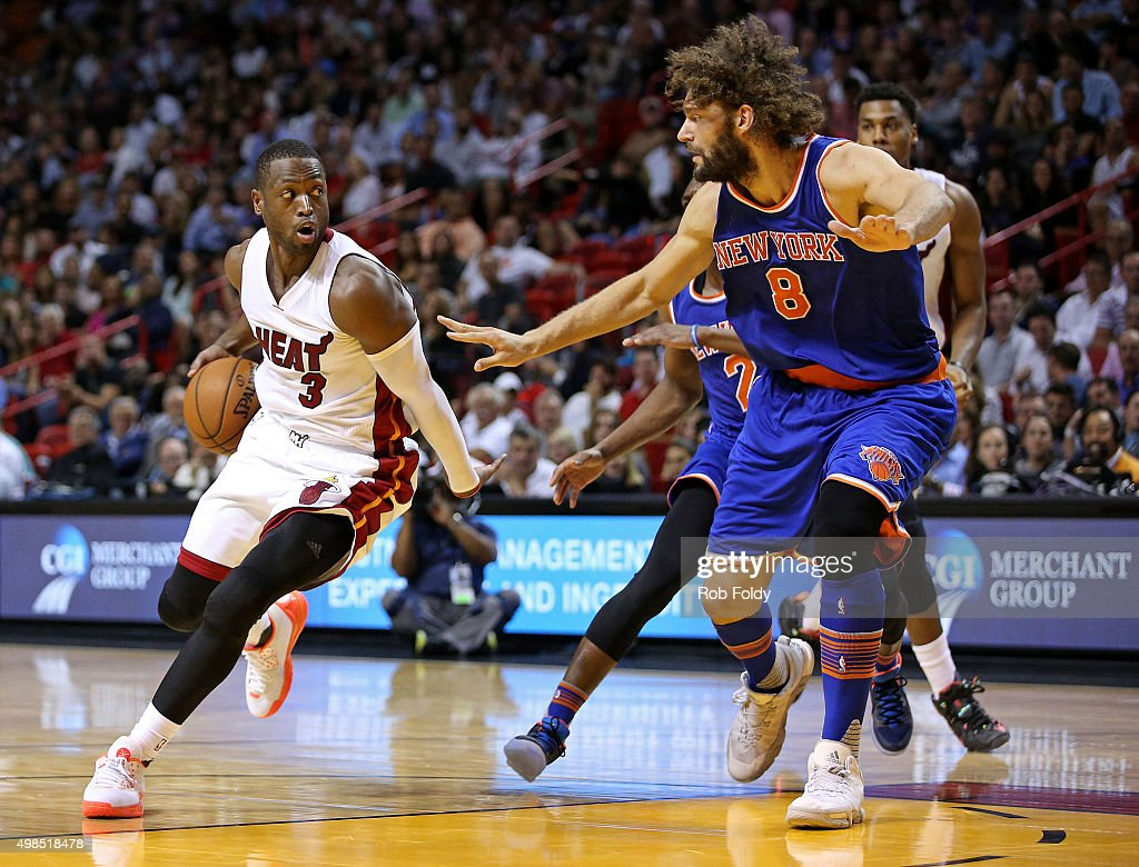 Dwyane Wade of the Miami Heat is defended by Robin Lopez of the New York Knicks during the game at American Airlines Arena on November 23 2015 in...