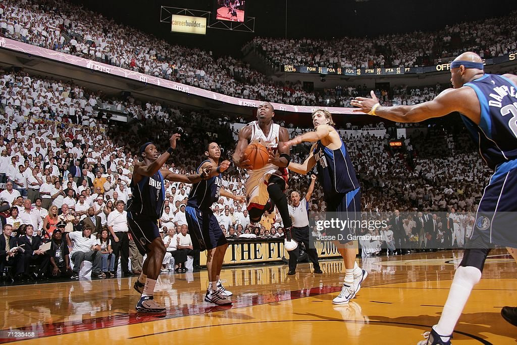 Dwyane Wade of the Miami Heat is fouled by Dirk Nowitzki of the Dallas Mavericks 19 seconds left in overtime Wade hit both of his free throws to win...