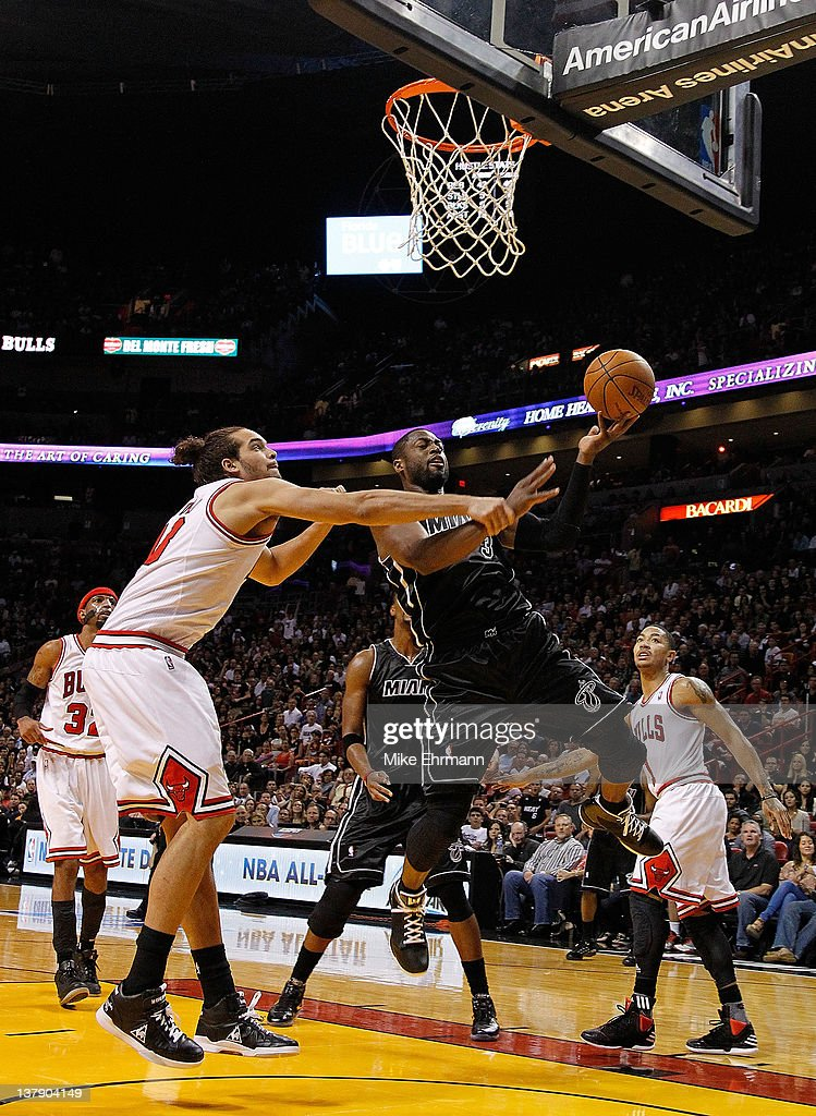 Dwyane Wade #3 of the Miami Heat is fouled by Joakim Noah #13 of the Chicago Bulls during a game at American Airlines Arena on January 29, 2012 in Miami, Florida.