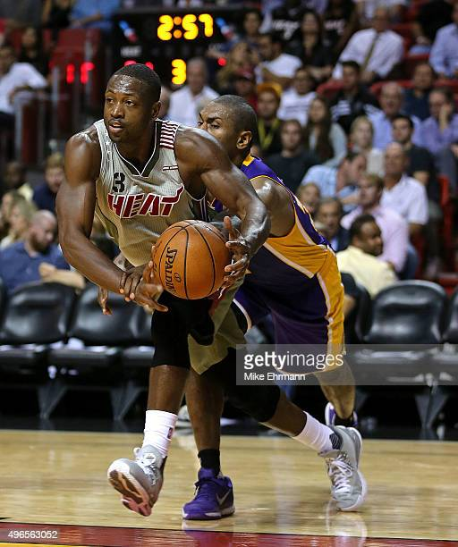 Dwyane Wade of the Miami Heat is fouled by Metta World Peace of the Los Angeles Lakers during a game at American Airlines Arena on November 10 2015...