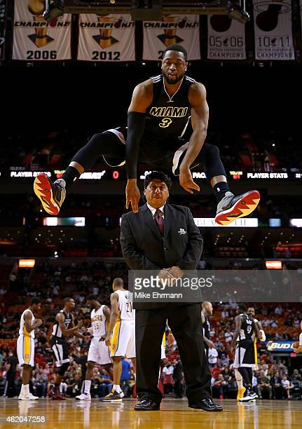 Dwyane Wade of the Miami Heat jumps over a security guard during a game against the Indiana Pacers at American Airlines Arena on January 23 2015 in...