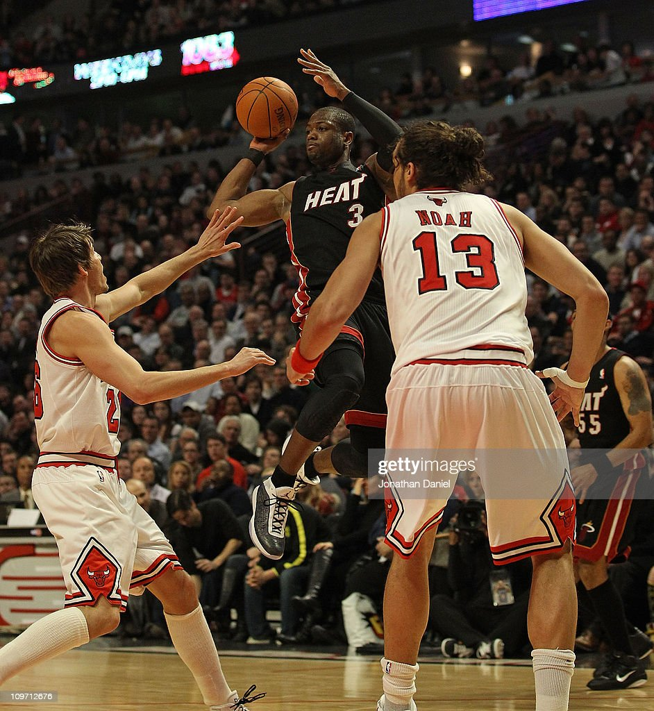 <a gi-track='captionPersonalityLinkClicked' href=/galleries/search?phrase=Dwyane+Wade&family=editorial&specificpeople=201481 ng-click='$event.stopPropagation()'>Dwyane Wade</a> #3 of the Miami Heat leaps to pass over Kyle Krover #26 and <a gi-track='captionPersonalityLinkClicked' href=/galleries/search?phrase=Joakim+Noah&family=editorial&specificpeople=699038 ng-click='$event.stopPropagation()'>Joakim Noah</a> #13 of the Chicago Bulls at the United Center on February 24, 2011 in Chicago, Illinois. The Bulls defeated the Heat 93-89.