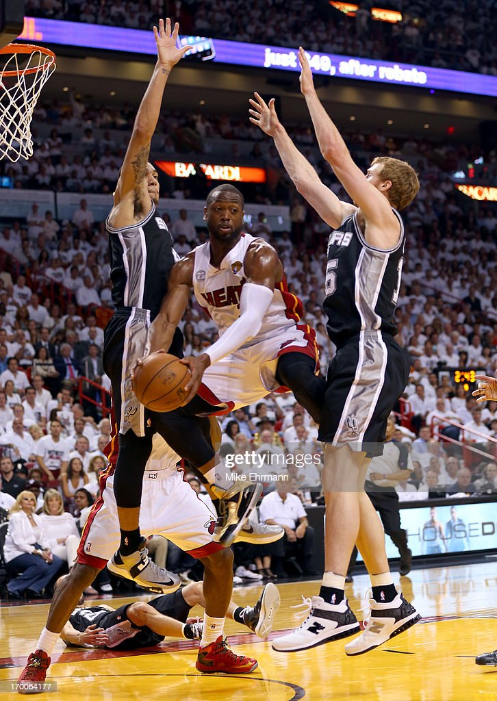 Dwyane Wade #3 of the Miami Heat looks to pass the ball between Danny Green #4 and Matt Bonner #15 of the San Antonio Spurs in the second quarter during Game One of the 2013 NBA Finals at AmericanAirlines Arena on June 6, 2013 in Miami, Florida.