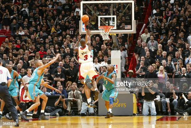 Dwyane Wade of the Miami Heat makes the game winning shot as Baron Davis of the New Orleans Hornets looks on during the 2004 NBA Playoffs on April 18...