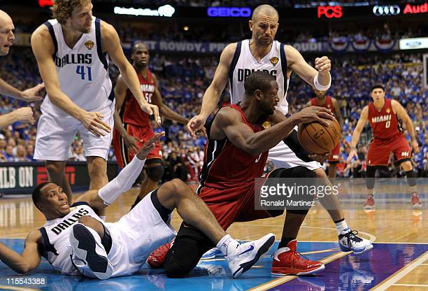 Dwyane Wade of the Miami Heat moves the ball on one knee between Shawn Marion and Jason Kidd of the Dallas Mavericks in the third quarter of Game...