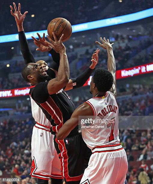 Dwyane Wade of the Miami Heat puts up a shot between Taj Gibson and Justin Holiday of the Chicago Bulls at the United Center on March 11 2016 in...