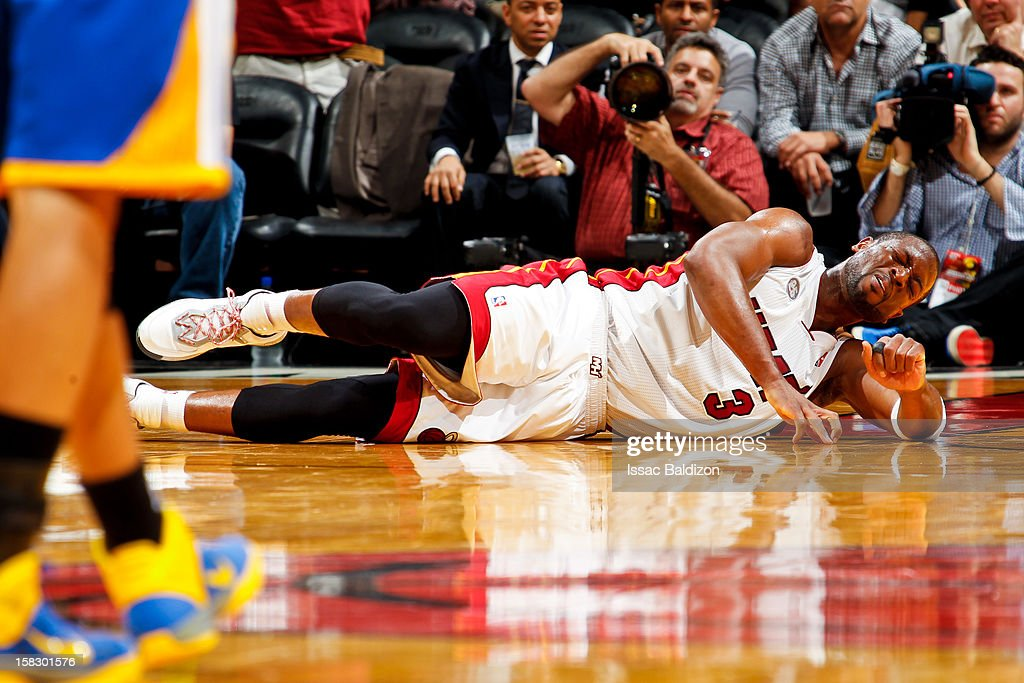 Dwyane Wade #3 of the Miami Heat reacts after getting hurt while playing the Golden State Warriors on December 12, 2012 at American Airlines Arena in Miami, Florida.
