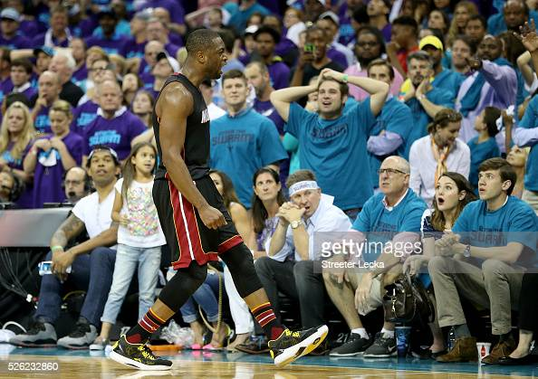 Dwyane Wade of the Miami Heat reacts after making a shot late in the fourth quarter against the Charlotte Hornets during game six of the Eastern...