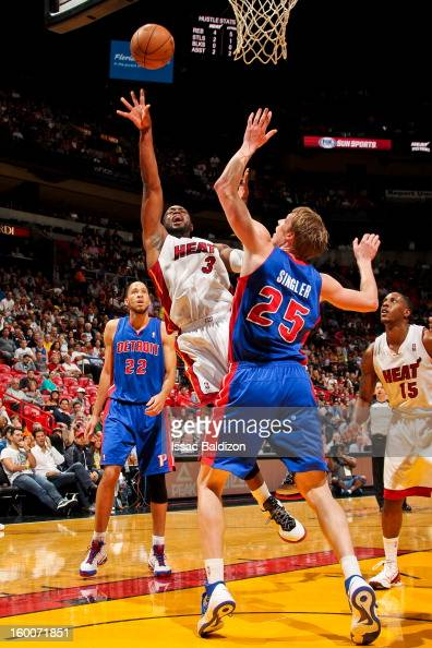 Dwyane Wade of the Miami Heat shoots a layup against Kyle Singler of the Detroit Pistons on January 25 2013 at American Airlines Arena in Miami...