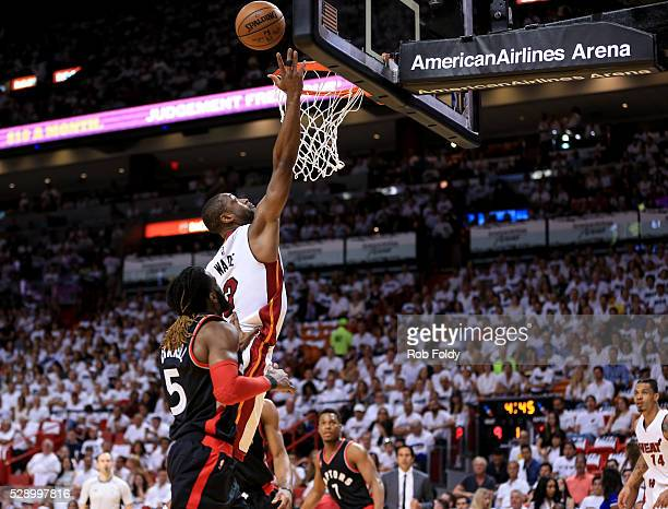 Dwyane Wade of the Miami Heat shoots a layup past DeMarre Carroll of the Toronto Raptors during the first quarter of the game at American Airlines...