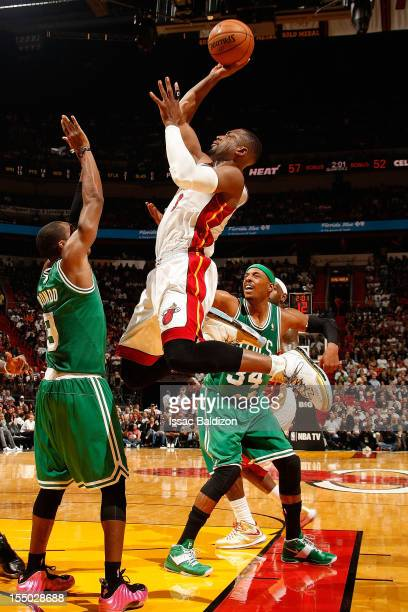 Dwyane Wade of the Miami Heat shoots against Rajon Rondo of the Boston Celtics during the NBA game on October 30 2012 at American Airlines Arena in...