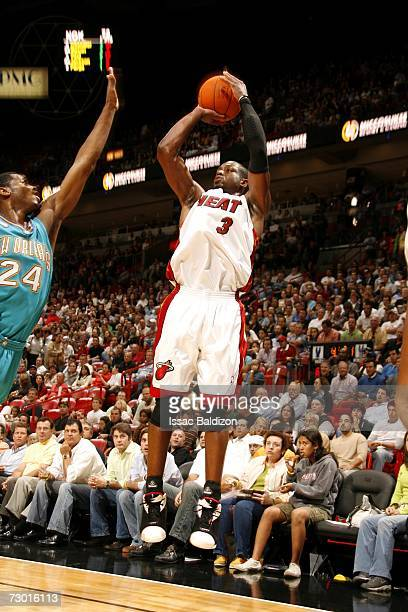 Dwyane Wade of the Miami Heat shoots over Desmond Mason of the New Orleans/Oklahoma City Hornets during the game at American Airlines Arena on...