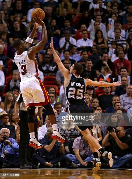 Dwyane Wade of the Miami Heat shoots over Nando de Colo of the San Antonio Spurs during a game at American Airlines Arena on November 29 2012 in...