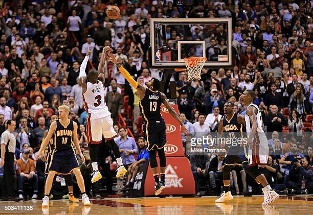 Dwyane Wade of the Miami Heat shoots over Paul George of the Indiana Pacers during a game at American Airlines Arena on January 4 2016 in Miami...
