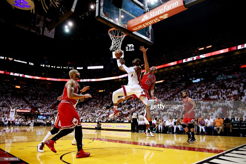 <a gi-track='captionPersonalityLinkClicked' href=/galleries/search?phrase=Dwyane+Wade&family=editorial&specificpeople=201481 ng-click='$event.stopPropagation()'>Dwyane Wade</a> #3 of the Miami Heat shoots past <a gi-track='captionPersonalityLinkClicked' href=/galleries/search?phrase=Joakim+Noah&family=editorial&specificpeople=699038 ng-click='$event.stopPropagation()'>Joakim Noah</a> #13 and <a gi-track='captionPersonalityLinkClicked' href=/galleries/search?phrase=Carlos+Boozer&family=editorial&specificpeople=201638 ng-click='$event.stopPropagation()'>Carlos Boozer</a> #5 of the Chicago Bulls during Game One of the Eastern Conference Semifinals of the 2013 NBA Playoffs at American Airlines Arena on May 6, 2013 in Miami, Florida.