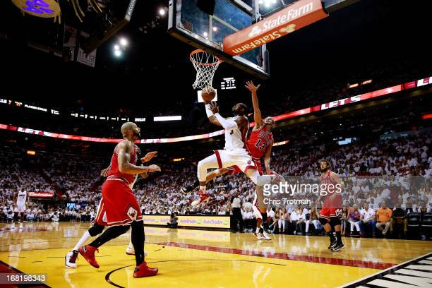 Dwyane Wade of the Miami Heat shoots past Joakim Noah and Carlos Boozer of the Chicago Bulls during Game One of the Eastern Conference Semifinals of...