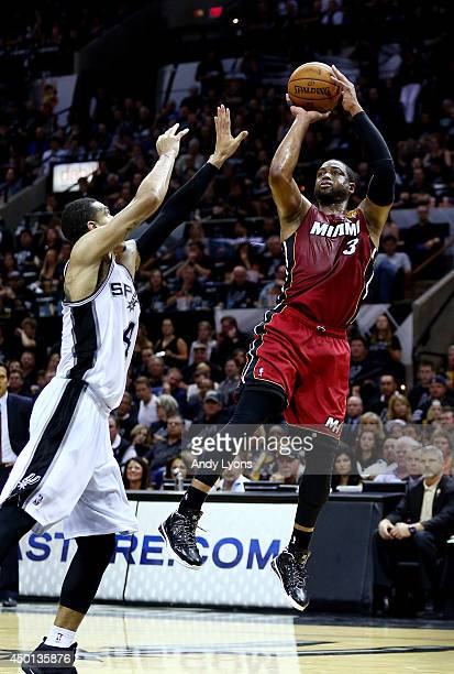 Dwyane Wade of the Miami Heat takes a shot over Danny Green of the San Antonio Spurs during Game One of the 2014 NBA Finals at the ATT Center on June...