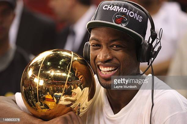 Dwyane Wade of the Miami Heat talks to the media while holding the Larry O'Brien NBA Championship Trophy after his team wins the NBA Championship by...