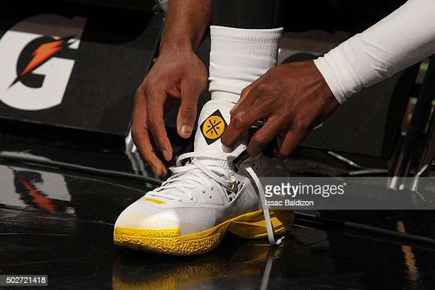 Dwyane Wade of the Miami Heat ties his shoes before the game against the Brooklyn Nets on December 28 2015 at American Airlines Arena in Miami...