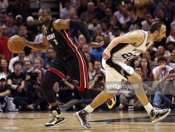 Dwyane Wade of the Miami Heat with the ball against Manu Ginobili of the San Antonio Spurs in the fourth quarter during Game Four of the 2013 NBA...