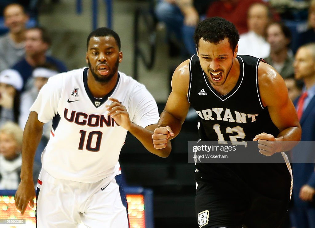 Dyami Starks of the Byrant Bulldogs celebrates his three point shot in the first half next to Sam Cassell Jr #10 of the Connecticut Huskies during...