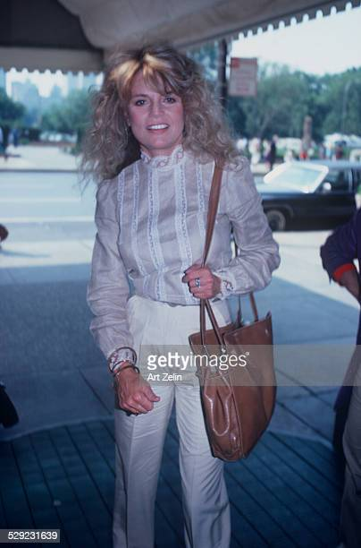 Dyan Cannon wearing a white casual outfit under a marquee circa 1970 New York