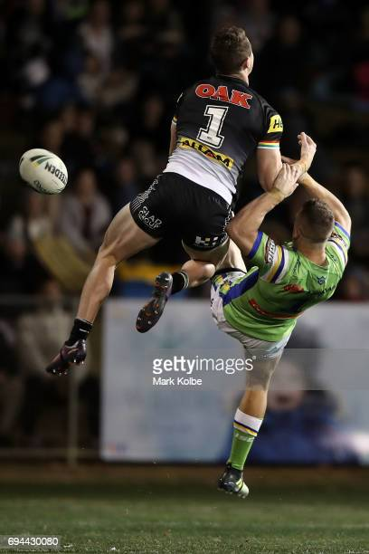 Dylan Edwards of the Panthers and Jack Wighton of the Raiders compete for the ball from a kick during the round 14 NRL match between the Penrith...