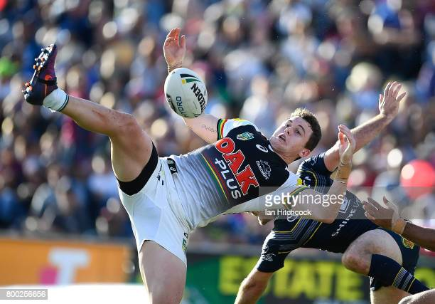 Dylan Edwards of the Panthers and Lachlan Coote of the Cowboys contest a high ball during the round 16 NRL match between the North Queensland Cowboys...