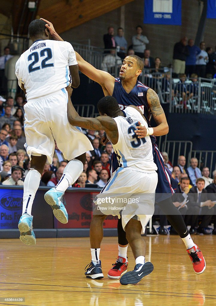 Dylan Ennis #31 of the Villanova Wildcats tries to push away Henry Brooks #3 of the Pennsylvania Quakers as he puts his hand on the face of JayVaughn Pinkston #22 at the Pavilion on December 4, 2013 in Villanova, Pennsylvania. Villanova won 77-54.