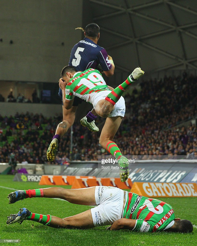 Dylan Farrell of the Rabbitohs falls to the ground injured as Mahe Fonua of the Storm and Andrew Everingham of the Rabbitohs compete for a high ball during the round 22 NRL match between the Melbourne Storm and the South Sydney Rabbitohs at AAMI Park on August 9, 2013 in Melbourne, Australia.