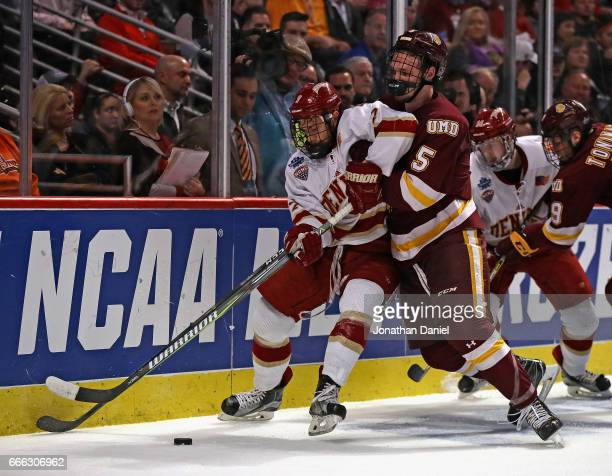 Dylan Gambrell of the Denver Pioneers and Nick Wolff of the MinnesotaDuluth Bulldogs battle for the puck during the 2017 NCAA Division I Men's Ice...