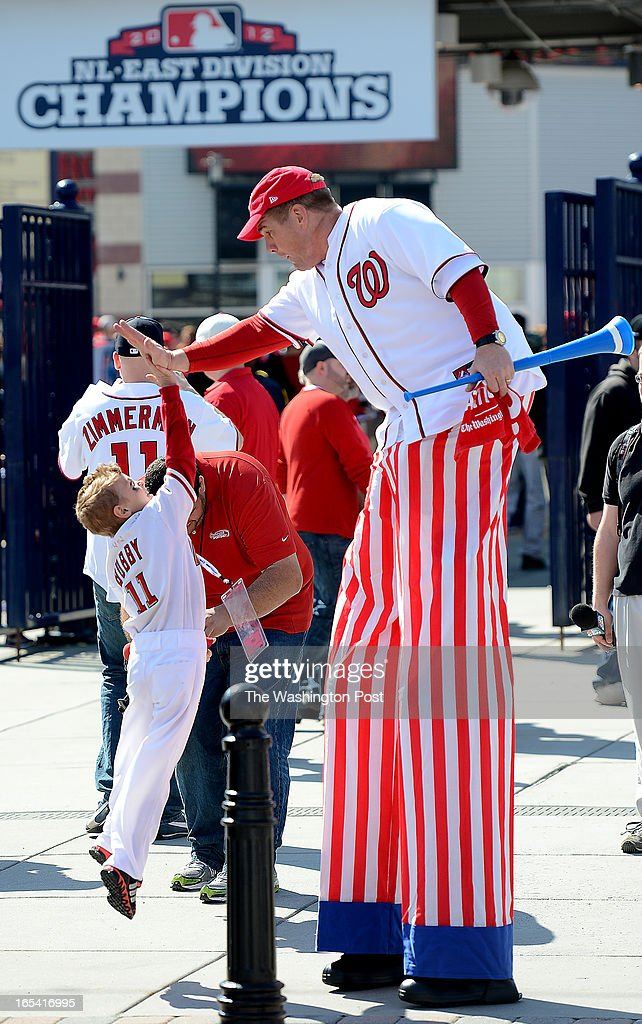 Dylan Gordon, 7, (cq from mom), of Washington, D.C. jumps to high five stilt walker Mark Lohr outside of the stadium before the start of the Opening Day game at Nationals Park on Monday, April 1, 2013.