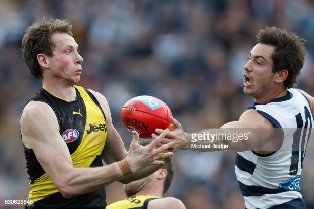 Dylan Grimes of the Tigers and Daniel Menzel of the Cats compete for the ball during the round 21 AFL match between the Geelong Cats and the Richmond...