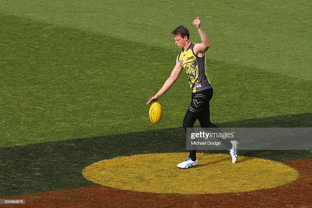 Dylan Grimes of the Tigers kicks the ball on the Aboriginal Flag painted on the ground during a Richmond Tigers AFL training session at ME Bank Centre on May 27, 2016 in Melbourne, Australia. This Round of the AFL is Indigineous Round.